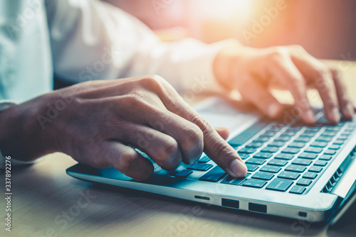 Obraz na plátně Businessman hand typing on computer keyboard of a laptop computer in office