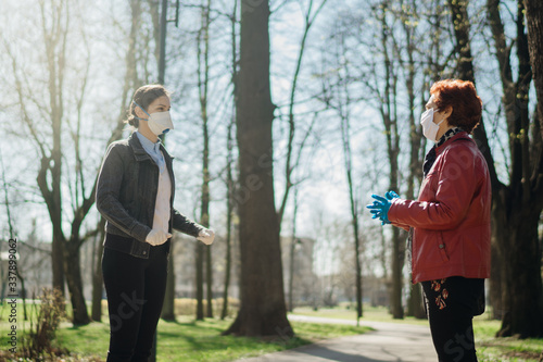 Fotomural Elderly woman with protective face mask/gloves talking with a friend