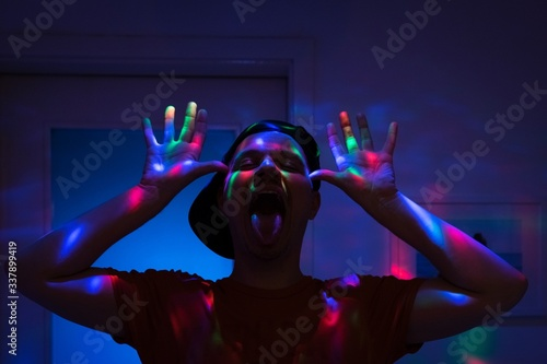 Photo Young Sticking Out Tongue While Standing In Illuminated Rood