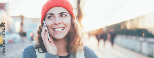 Fototapeta Smiling curly woman talking on the mobile phone on the street