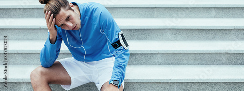 Upset athlete after failure workout sitting on the stairs on the street and hold Fototapet