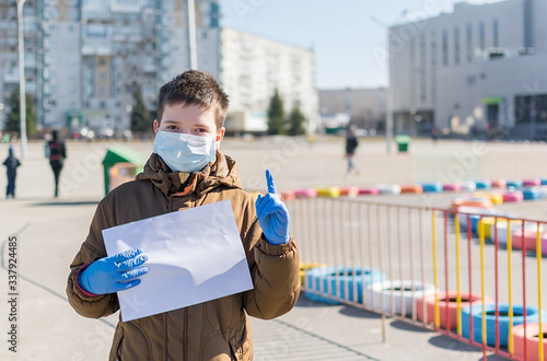 a child in a medical anti virus mask in a quarantined city amusement Park holds Wallpaper Mural