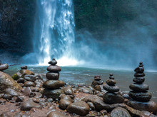 Stones Stacked By River Against Waterfall