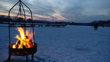 Bonfire On Snowcapped Landscape Against Sky During Dusk