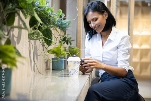 Foto Young businesswoman using smartphone in coffee shop