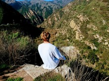 Single Young Man Sitting On A Rock Precipice Enjoying The Outdoor Scenic Beauty Over Looking Malibu Canyon And Mountains, A Popular Tourist Place To Visit And Hike Because Of Its Beautiful Scenery