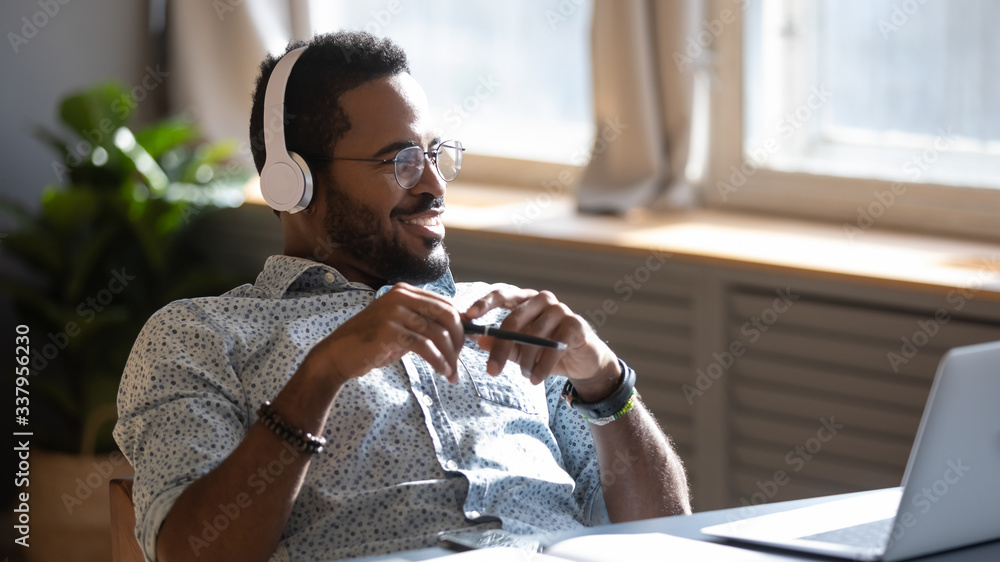 Fototapeta Distracted from job study happy millennial african american man in glasses listening to favorite audio music, looking away, thinking of future, enjoying pause break time alone at workplace home.
