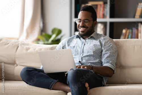 Obraz Smiling young african american man in eyewear relaxing on couch, looking at laptop screen. Happy multiracial guy web surfing internet, chatting with friends in social network, watching movie at home. - fototapety do salonu