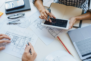 engineer Hand Drawing Plan On Blue Print with architect equipment discussing the floor plans over blueprint architectural plans at table in a modern office.