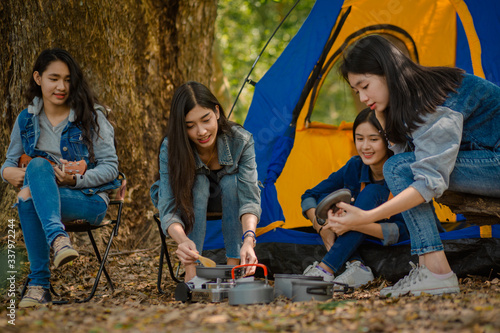 Group of happy friends enjoying picnic while cooking a meal near camping, Cheerf Canvas Print