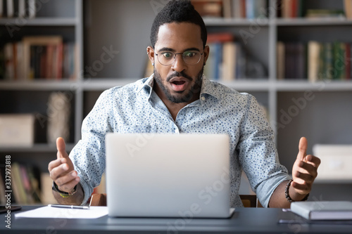 Fototapety, obrazy: Front view shocked millennial african american man in glasses looking at laptop screen, received email with unbelievable news. Frustrated young mixed race guy worrying of bad surprise or problem.