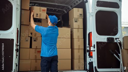 Courier Takes out Cardboard Box Package from Delivery Van Full of Parcels, Delivering Postal Parcel Fototapete
