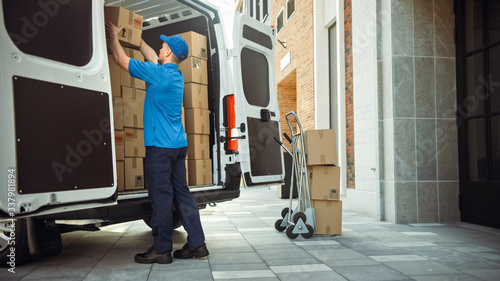 Obraz Delivery Man Uses Hand Truck Trolley Full of Cardboard Boxes and Packages, Loads Parcels into Truck / Van. Professional Courier / Loader helping you Move, Delivering Your Purchased Items Efficiently - fototapety do salonu