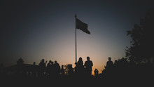 Silhouette People Standing By Flag During Sunset