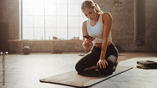 Beautiful and Young Girl Uses Smartphone App During Her Exercise on Fitness Mat Slika na platnu