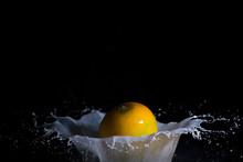 Close-up Of Fruit In Splashing Milk Against Black Background