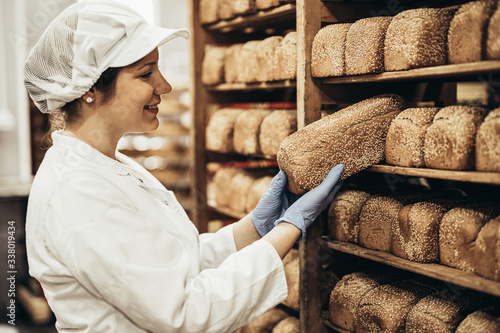 Obraz na plátně Young female worker working in bakery. She puts bread on shelf.