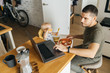 Feeding a baby in a modern family. Male Dad and his daughter in the kitchen interior. Remote work and difficulties of education.