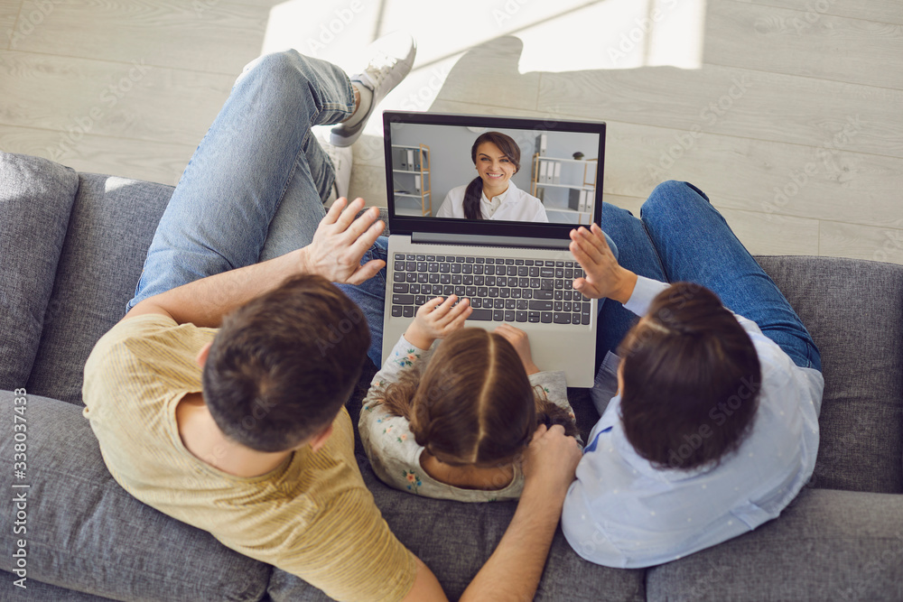 Fototapeta Family doctor online. Family talking consults a doctor using a laptop while sitting at home on the couch.