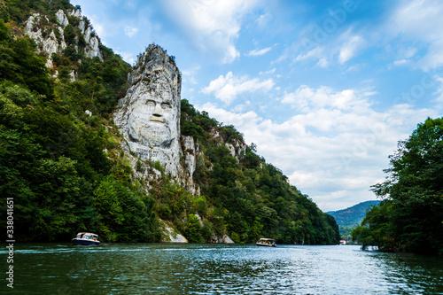 Obraz The face of the Dacian king Decebal. Panoramic view of the Danube river.  - fototapety do salonu