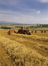 Old Image Of Straw Bailing By An Old Vintage Tractor In Somerset , UK