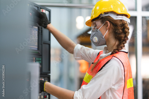 Female Engineer wear face mask with safety vest and yellow helmet operating cont Fototapet
