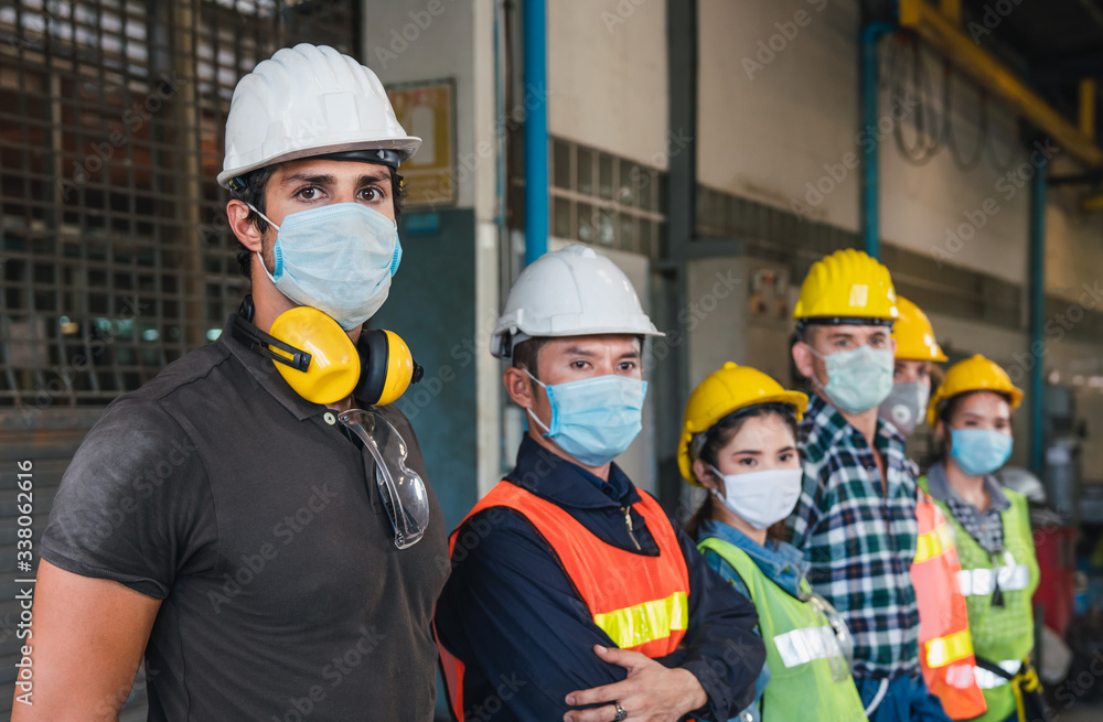 Fototapeta Group of diverse team of workers wearing face mask and protective helmets standing in front of the factory