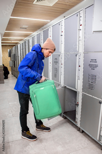 Photo A young man is putting suitcase into locker box in transport terminal