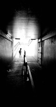 Mid Distance View Of Boy Standing On Footpath Seen Through Tunnel