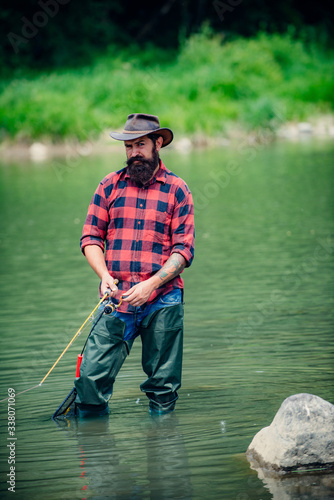 Photo Man relaxing and fishing by lakeside