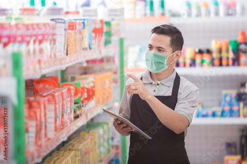 Photo asian male shopkeeper working in a grocery store