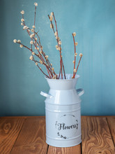 A Bouquet Of Willow In A Blue Tall Planter Stands On A Wooden Table