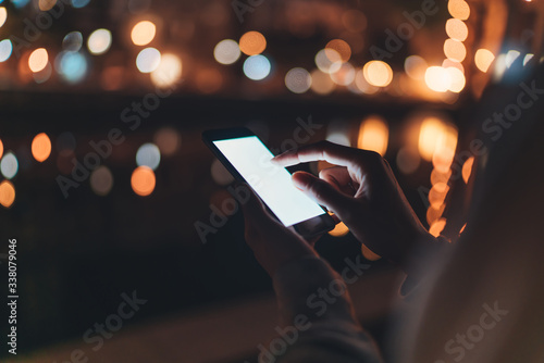 Foto person texting text message on smartphone light night city, hipster touch on tem