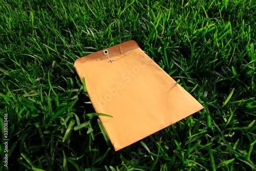 Photo yellow envelope eon the grass