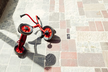 High Angle View Of Red Tricycle Fallen On Tiled Floor