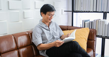 Senior Asian Man Reading Book On Sofa In Living Room At Home ,Portrait Of Asian Elderly Man Is Relaxing And Happiness With Read A Magazine  At Home