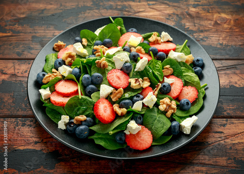 Fototapeta Spinach, Strawberry, blueberry salad with walnut and feta cheese. Summer healthy food obraz