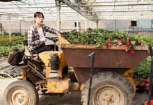 Portrait Of Chinese Female Farmer Working On Farm Tractor In Greenhouse