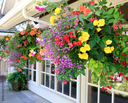 Fotografía Blooming flowers amazing complex baskets hanging pots near small luxury lodge exterior