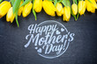 Happy Mother's Day! Flat lay yellow tulips on black background
