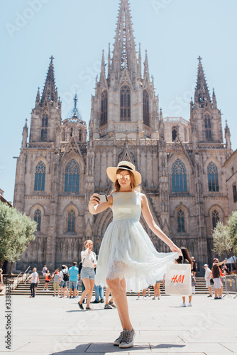 Photo Young and happy tourist woman making selfie photo in front of cathedral in Barce