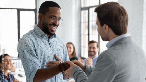 Cuadros en Lienzo Caucasian businessman handshake African American male employee congratulate with