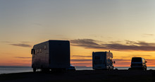 Campervans Silhouettes Against Colourful Sky