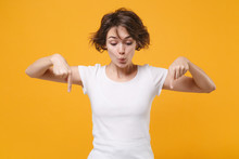 Amazed Young Brunette Woman In White T-shirt Posing Isolated On Yellow Orange Wall Background Studio Portrait. People Sincere Emotions Lifestyle Concept. Mock Up Copy Space. Point Index Fingers Down.