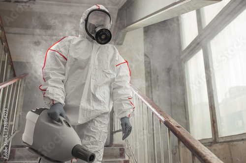 Obraz professional disinfector in protective suit holding chemical sprayer and other equipment for sterilization and decontamination of viruses, infectious diseases. coronavirus, COVID-19 epidemic concept - fototapety do salonu