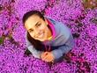 Leinwandbild Motiv Portrait Of Smiling Woman Standing Amidst Purple Flowers