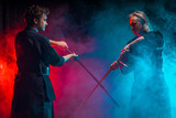 two caucasian Kendo martial arts fighters combat fighting in silhouette isolated colorful smoky space, neon lights. fight, kendo concept