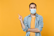 Young man in sterile face mask posing isolated on yellow background studio portrait. Epidemic pandemic spreading coronavirus 2019-ncov sars covid-19 flu virus concept. Pointing index finger aside up.