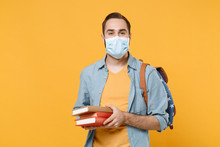 Young Man In Sterile Face Mask With Backpack Posing Isolated On Yellow Wall Background In Studio. Epidemic Pandemic Rapidly Spreading Coronavirus 2019-ncov Sars Covid-19 Flu Virus Concept. Hold Books.