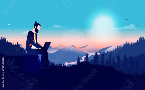 Fotografie, Obraz Remote work from anywhere - Man sitting alone in nature wilderness working on laptop